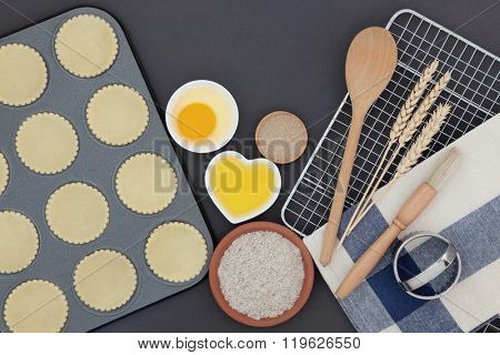 Pastry dough shapes in baking tray with ingredients and utensils over grey background.