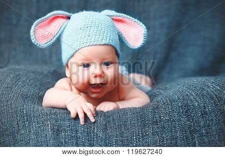 Happy Baby Child In Costume A Rabbit Bunny   On A Grey