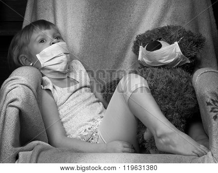 Small child with a toy bear cub in a medical mask
