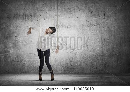 Asian business woman hace string attached on her body like marionette. Business manipulated concept poster