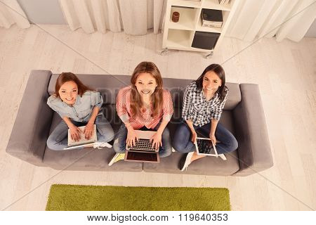 Top View Photo Of Three Girls Holding A Laptop And Digital Tablet