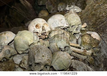 Tana Toraja, Indonesia - Dec 08, 2015: Pile of skulls by the entrance to Tampang Allo burial cave of the royal family. There are coffins are placed in caves or hanging from the cliff and wooden statues tau-tau guard the graves. Tana Toraja. South Sulawesi
