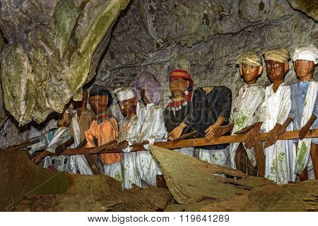 Tana Toraja, Indonesia - Dec 08, 2015: Wooden statues of Tau Tau in Tampang Allo burial cave of the royal family. There are pile of skulls by the entrance coffins are placed in caves or hanging from the cliff. Tana Toraja. South Sulawesi. Indonesia