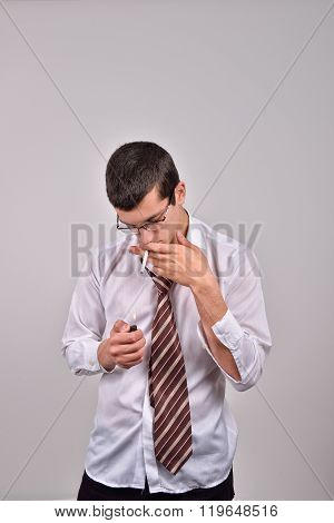 Stressed Young Businessman Lighting Cigarette In Studio