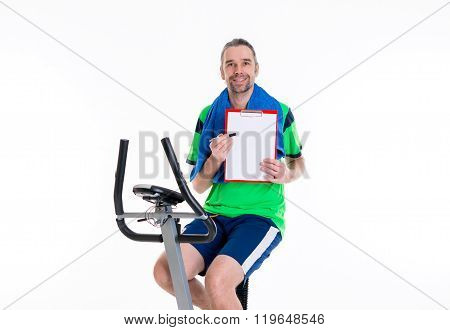 Young Man With Clipboard Train On Fitness Machine