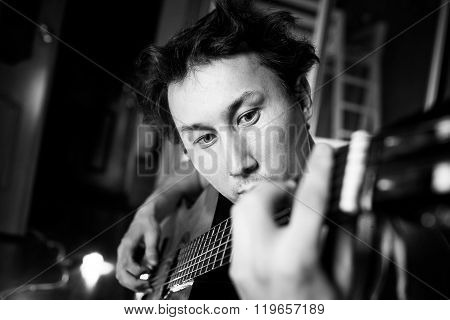 Crazy passionate guitarist playing guitar, black and white close-up portrait.