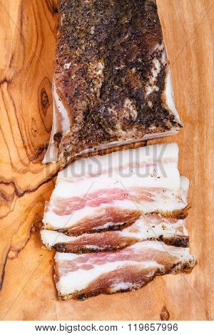 Top View Of Piece And Few Slices Of Bacon On Board