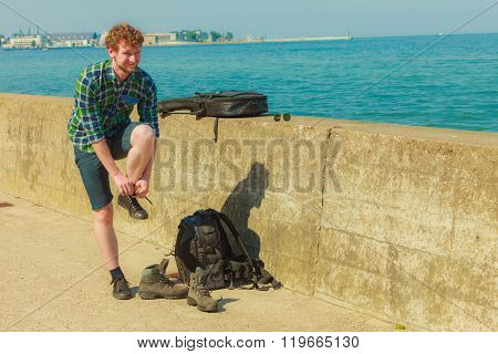 Young Man With Backpack Hikiner On Sea Coast