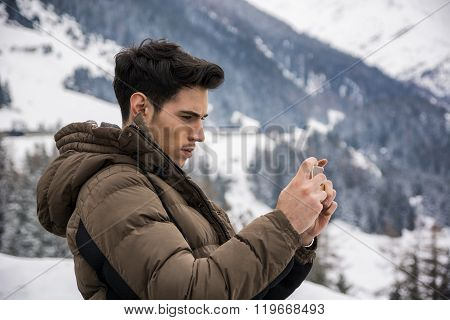 Young man in outerwear taking photo of landscape