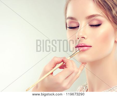 Makeup artist paints her lips a beautiful and gentle girl .