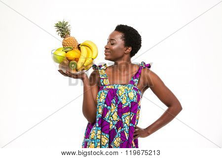 Smiling beautiful african american young woman in colorful sundress standing and posing with glass bowl with exotic fruits over white background