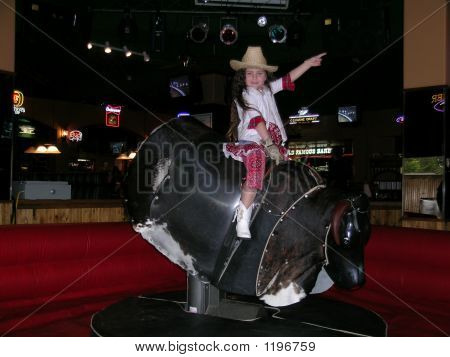 young girl rides a mechanical bull in a country and western restaurant poster