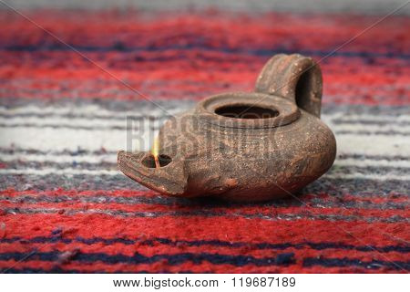 Ancient oil lamp from Israel over colorful textile