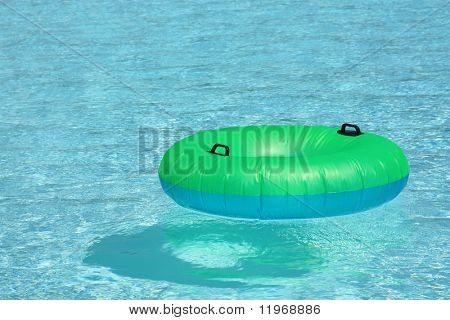 Green and blue tube floating in a pool