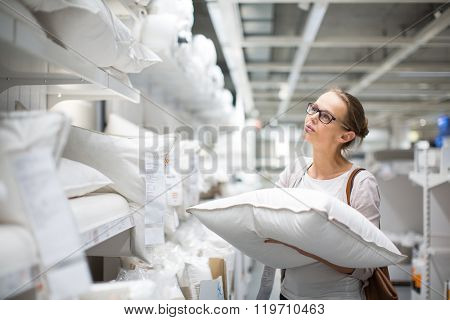 Pretty, young woman choosing the right pillow for her bed in a modern home furnishings store (color toned image; shallow DOF)