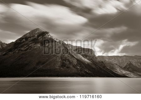 Lake Minnewanka in Banff national park with mountains and forest in Canada at sunrise.