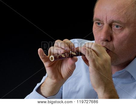 Mature musician playing Ukrainian woodwind instrument sopilka