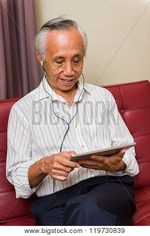 Senior Male Using Technology For Entertainment