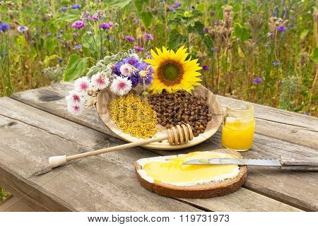 A sandwich with honey in front of a wooden plate with apiculture products and flowers ** Note: Shallow depth of field