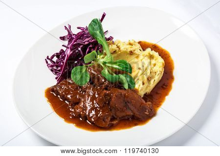 Cooked veal cheeks in gravy with potatoes and cabbage, decorated fresh herbs in white plate. Close-up poster