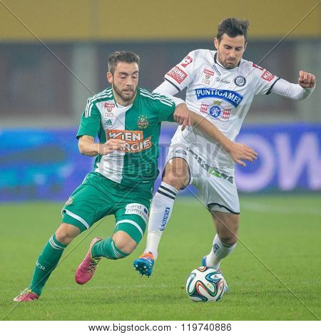 VIENNA, AUSTRIA - OCTOBER 29, 2014: Josip Tadic (#11 Sturm) and Thanos Petsos (#5 Rapid) fight for the ball in an Austrian soccer league game.
