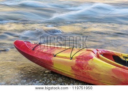 Bow of whitewater kayak on a river shore with a rapid in background