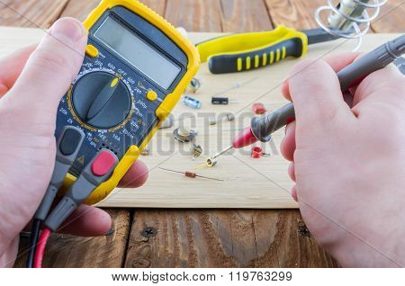 The Workplace Of Serviceman. Hands Holding The Multimeter.