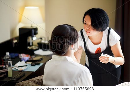 Makeup artist at work, asian woman doing makeup for bride, in morning. Wedding preparations.