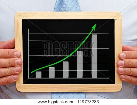 Sales Manager with business or performance chart on chalkboard