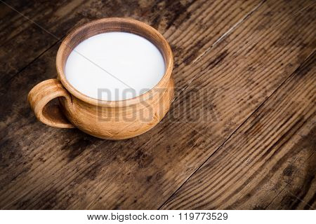 Milk In Vintage Cup On Old Wooden Table