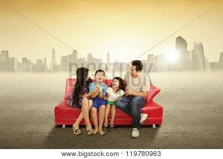 Cheerful Family Sitting On The Couch Outdoors