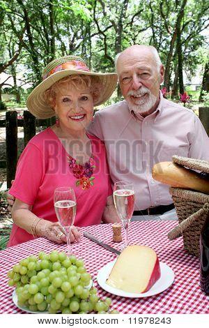 Ein attraktives senior paar genießen ein Picknick im Freien.