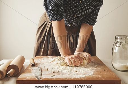 Woman kneads dough for pasta on wooden board near two rolling pins and jar with flour poster