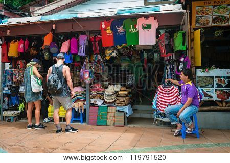 AO NANG KRABI THAILAND - 15 OCT 2014: Retail market stall selling souvenirs hats colorful balls and bags outside and the shop keeper sitting on a stool.