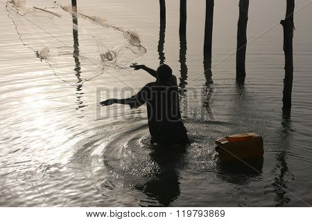 A fisherman throws out his net