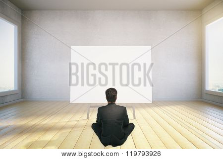 A Man Sits On The Floor And Looking At Blank Poster, Mock Up, 3D Render