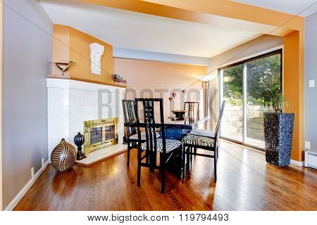 Dinning Room With White Fire Place, Hardwood Floor, And Orange Interior Paint.