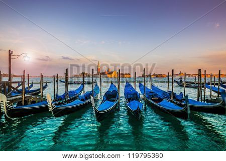 Gondolas in Venice - sunset with San Giorgio Maggiore church. San Marco, Venice, Italy. Intentional motion blur.