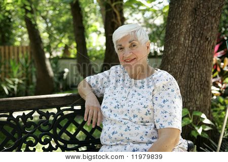 A sweet senior lady relaxing on a park bench.   Room for text.