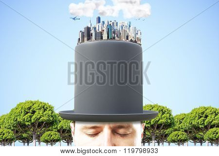 Man In Black Cylinder With 3D Megapolis City On The Top At Blue Sky Background