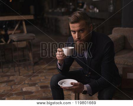 Attractive bearded businessman is enjoying hot coffee