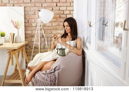 Young woman sitting in cosy bean bag chair, using mobilephone, drinking tea.