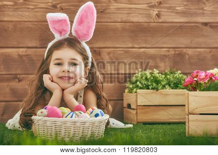 Cute little child girl wearing bunny ears on Easter day. Girl hunts for Easter eggs on the lawn near the house. Girl holding basket with painted eggs.