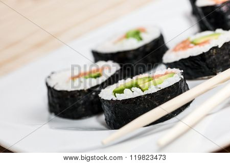 Sushi with salmon, avocado, rice in seaweed and chopsticks on a plate. Japanese, Asian healthy food.