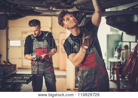 Profecional car  mechanics  working under lifted car in auto repair service.