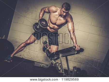 Athletic man doing exercises with dumbbells in The Gym's Studio