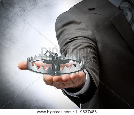 Businessman holding bear trap
