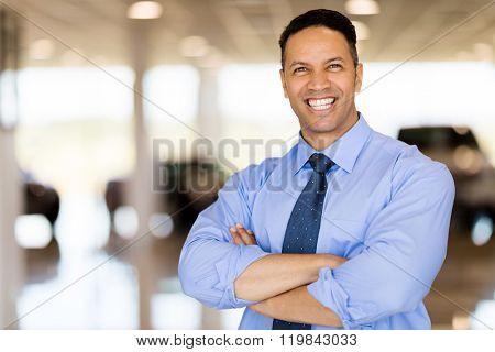 good looking male car dealer principal inside showroom