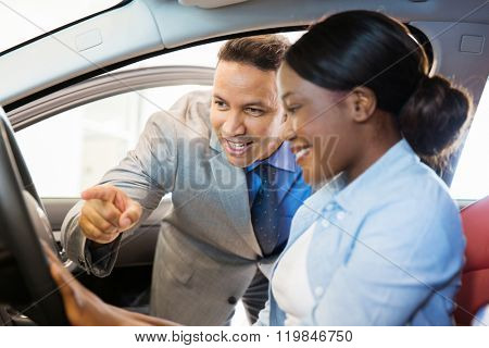 car sales consultant showing a new car to customer