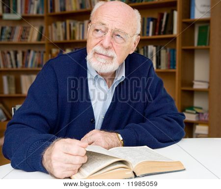 Senior man thinking about the book he is reading in the library.